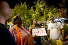 Surreace Cox, of North Charleston, S.C., holds a sign during a prayer vigil down the street from the Emanuel AME Church early Thursday, June 18, 2015, following a shooting Wednesday night in Charleston, S.C. (AP Photo/David Goldman)
