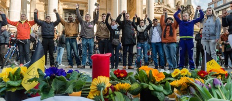 People hold hands in solidarity near a memorial to attack victims outside the stock exchange in Brussels on Tuesday, March 22, 2016. Explosions, at least one likely caused by a suicide bomber, rocked the Brussels airport and subway system Tuesday, prompting a lockdown of the Belgian capital and heightened security across Europe. (AP Photo/Geert Vanden Wijngaert)